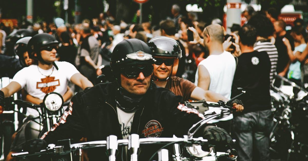 A man riding a motorcycle in front of a crowd